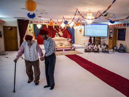 JJ Singh Kapur walks with his grandfather Amarjit inside