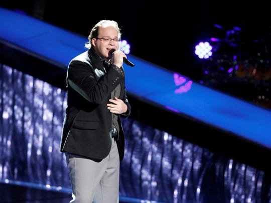"""Lansing native Lucas Holliday, 26, remains a contestant on NBC's """"The Voice.""""  On Monday, he survived the show's battle rounds."""