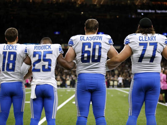 Lions players link arms during the national anthem before the game against the Saints at the Mercedes-Benz Superdome on Oct. 15, 2017 in New Orleans. Pictured are Jeff Locke (18), Theo Riddick (25), Graham Glasgow (60) and Emmett Cleary (77).