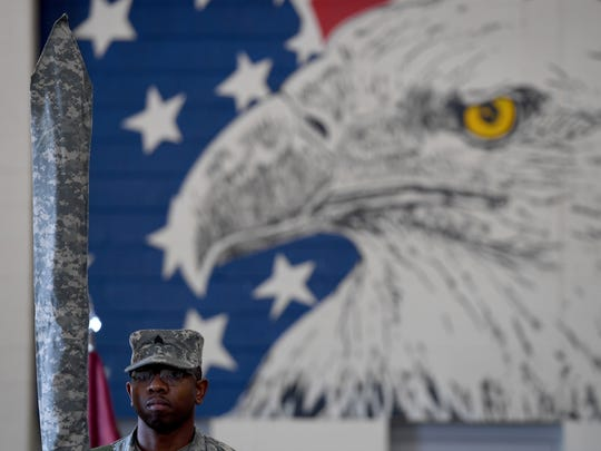 Sgt. Tyrone Scott Sr. stands in front of a mural of an American Bald Eagle  during the 30th Combat Sustainment Support Battalion deployment ceremony, Saturday, October 21, in Humboldt.