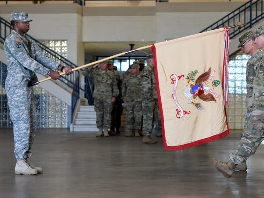 Sgt. Tyrone Scott Sr. presents the 30th Combat Sustatinment Support Battalion flag as CSM Michael Warren and LTC Brooke Grubb walk over to prepare to case the colors during their deployment ceremony, Saturday, October 21, in Humboldt.
