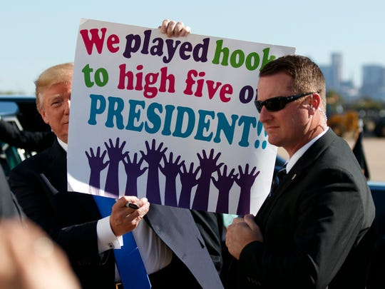 President Donald Trump holds a sign given to him by a crowd of supporters after landing at Dallas Love Field airport on Oct. 25, 2017, in Dallas.