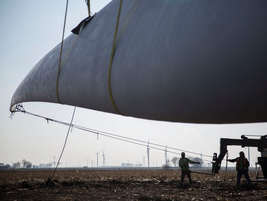 Workers from Mortenson Company attach a wind turbine