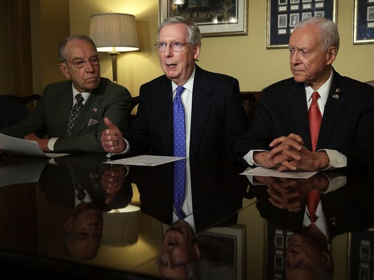 Senate Majority Leader Mitch McConnell speaks alongside Senate Finance Chairman Orrin Hatch and Sen. Chuck Grassley during a meeting with members of the Senate Finance Committee on Nov. 9, 2017.