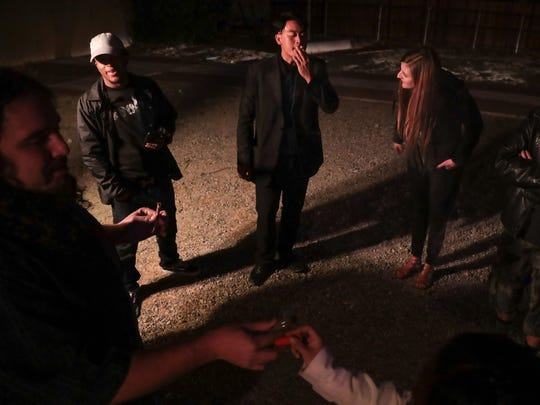 A group of friends smoke pot outside of a New Year's Eve party hosted by Vets Leaf in Desert Hot Springs, Calif., December 31, 2017.