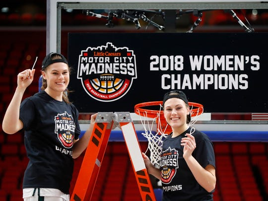 Green Bay's Madison Wolf and Mackenzie Wolf celebrate after their win in the Horizon League tournament championship game against Wright State at Little Caesars Arena on Tuesday.