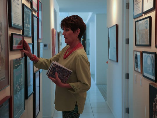 Lucie Arnaz adjusts a poster hanging in the hallway