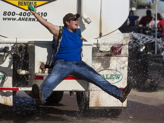 Max Lamadrid rides on the back of a water truck during