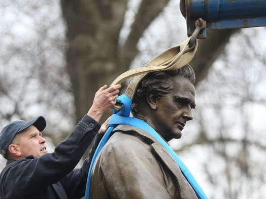 A parks department worker secures a statue of J. Marion Sims, before it is driven away.