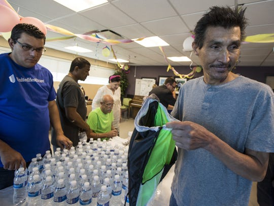 Enrique Duarte, a patient at Circle the City, helps stuff bags with toiletries and other items on Thursday, May 10, 2018 at Circle the City in Phoenix. United Health Foundation announced a three-year, $1 million partnership with Circle the City that will allow the organization to expand healthcare services in a renovated facility.