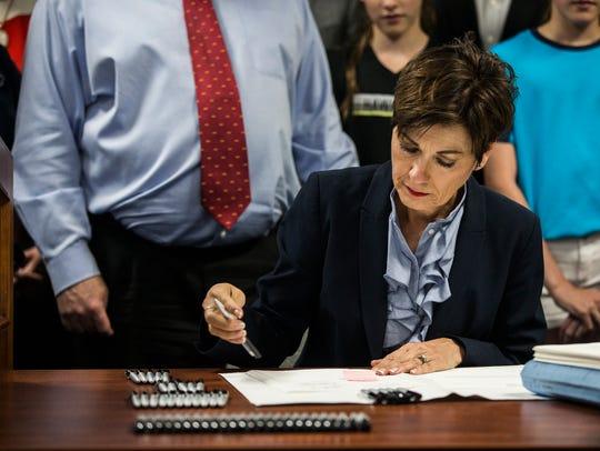 Iowa Governor Kim Reynolds signs the tax cut bill passed