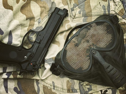 Airsoft protection mask, Terrorist mask and 9mm pistol (M9 Handgun) on camouflage background.