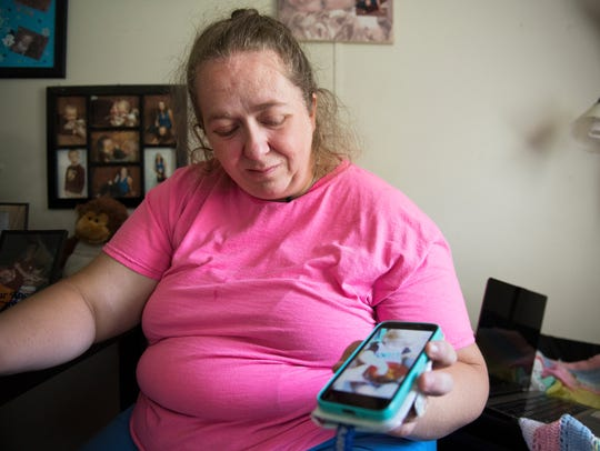 Krista Nix watches a video of her 18-month-old son,