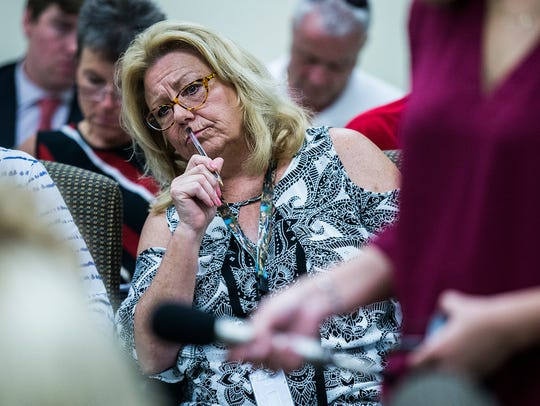 Pam Jochum, D-Dubuque, listens while Mike Randol, Iowa