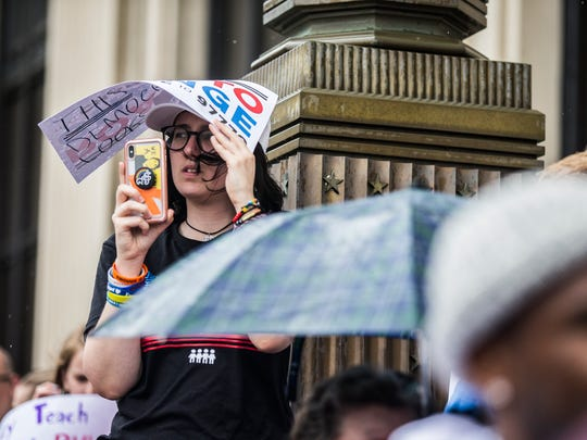Sofie Whitney, a graduate of Marjory Stoneman Douglas High School in Parkland, Florida and a March for Our Lives organizer, holds a sign over her head to block the rain during a demonstration in downtown Sioux City, on Wednesday, June 20, 2018. Sioux City was the first stop on the national movement's tour through Iowa this week.
