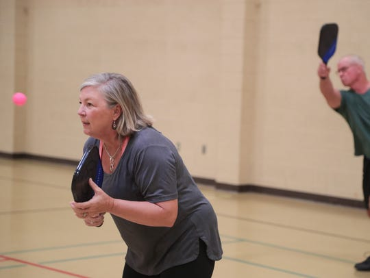 Cindy Montero plays pickleball with teammate Mike Brown