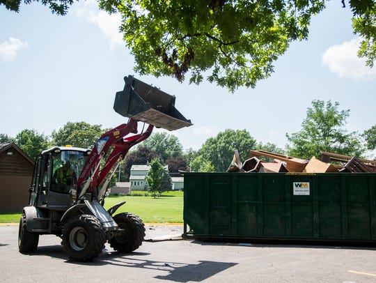 A city worker tries to make more space in a dumpster