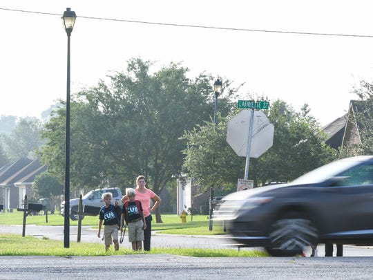 Students wait for the bus on Hwy. 89 in Youngsville, Louisiana, on Aug. 9, 2017.