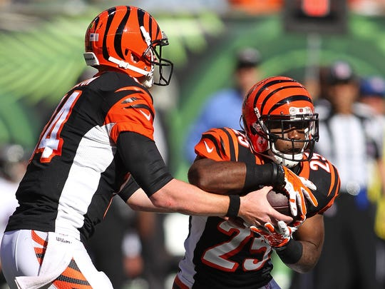 CINCINNATI, OH - OCTOBER 26:  Andy Dalton #14 of the Cincinnati Bengals hands the ball off to Giovani Bernard #25 of the Cincinnati Bengals during the third quarter of the game against the Baltimore Ravens at Paul Brown Stadium on October 26, 2014 in Cincinnati, Ohio. (Photo by John Grieshop/Getty Images)