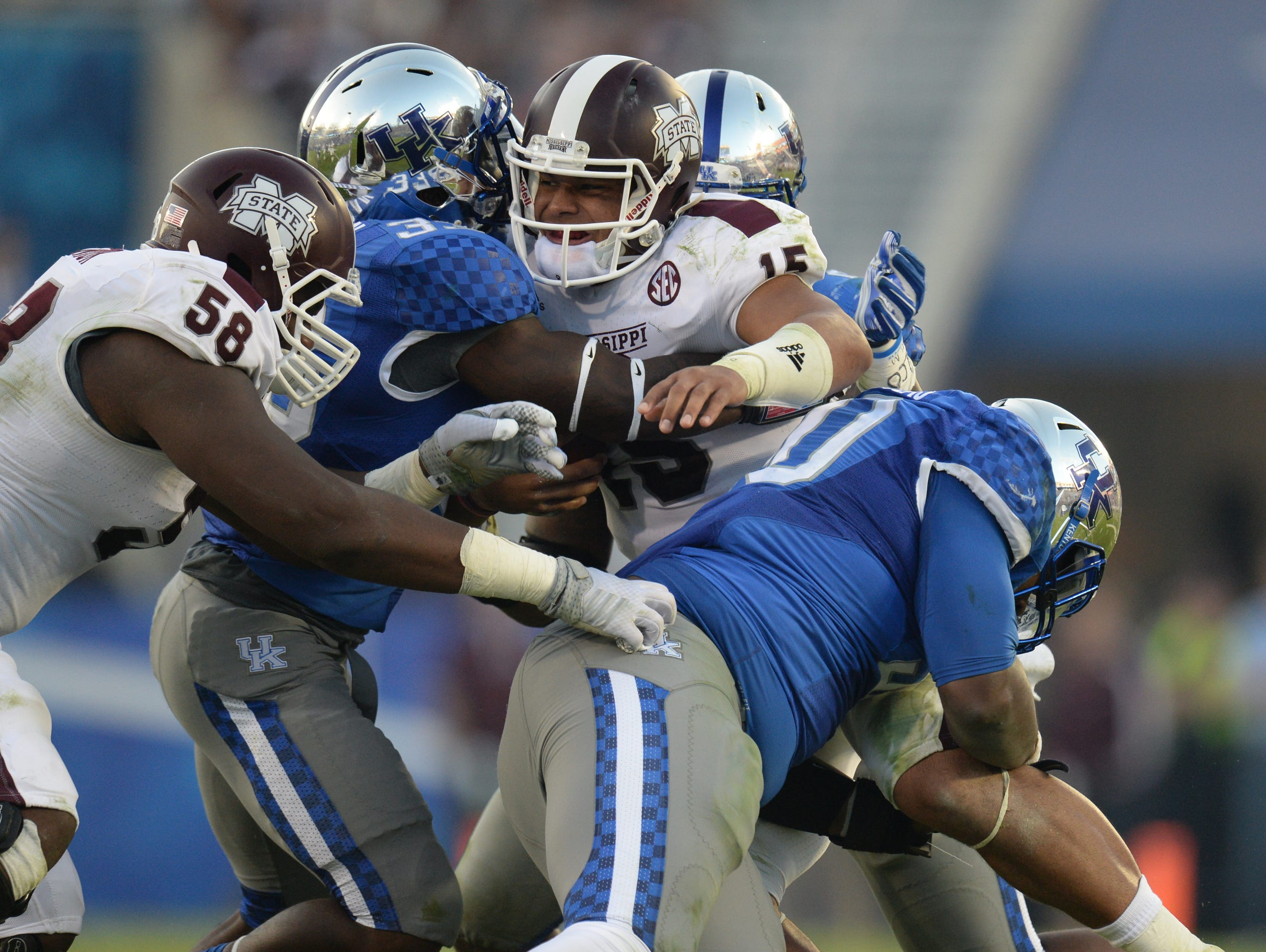 Mississippi State QB Dak Prescott is tackled by multiple UK defenders during the second half of the University of Kentucky football game against Mississippi State in Lexington, Ky. Saturday, October 25, 2014.