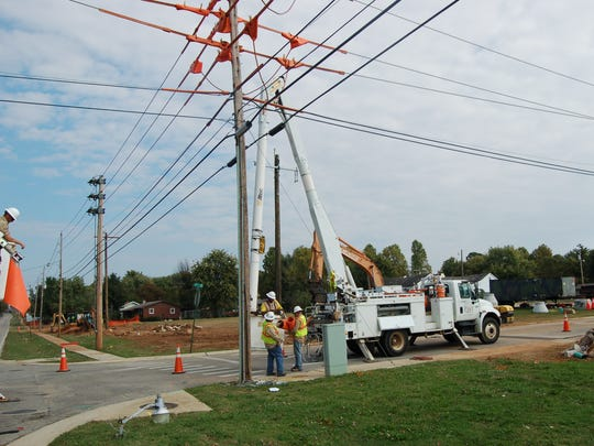 Work is done on a utility pole on Monday as part of the widening of AR Highway 201.