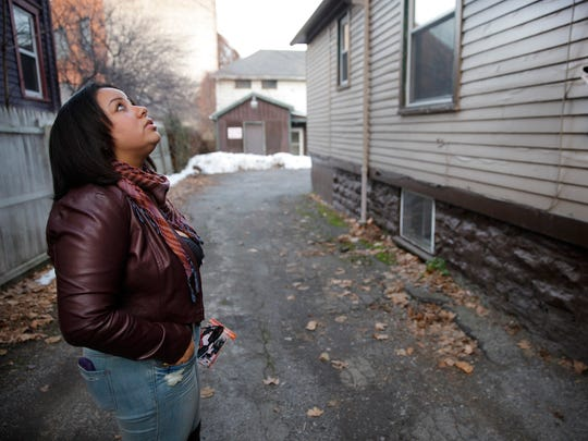 Erica Maldonado Rios looks up at the Birch Crescent apartment where she lived as a child with her young mother.