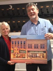 Capitol Civic Centre Executive Director Matthew Schliesman presents outgoing Board Vice President Christine D. Kornely with a canvas print of the Capitol Civic Centre.