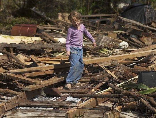 Above, Wendy Lynn Raffield, 5, plays on a debris pile