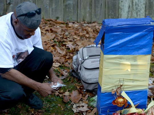 L'Sana DJahspora kneels next to a memorial set up for his son Cinque on Friday. Cinque was shot and killed by a Jackson police officer last year, and his family has filed a federal lawsuit against the city and police.
