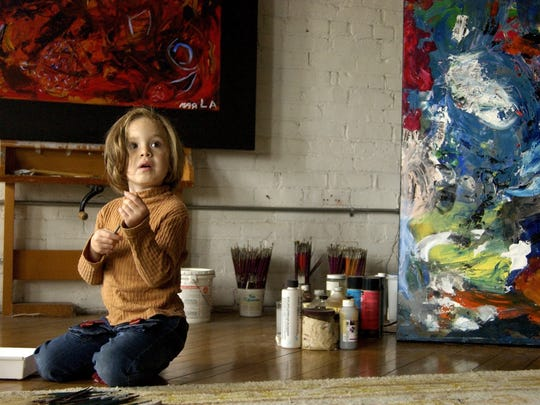 Marla Olmstead, shown here at age 4, plays with paint brushes next to her artwork at the Brunelli Art Gallery in Binghamton in 2004.