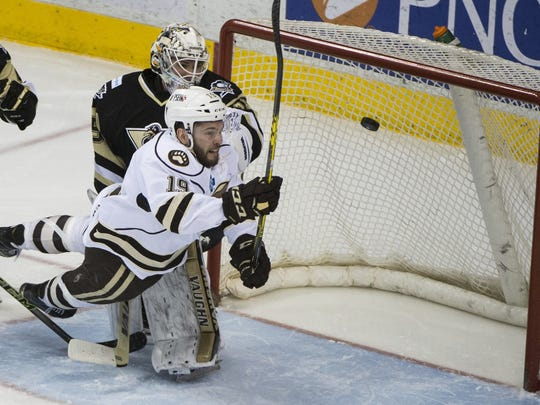 Hershey Bears right wing Riley Barber (19) tries to knock the puck out out the air and beat Wilkes-Barre/Scranton goalie Tristan Jarry (35). The Bears defeated the Penguins 5-3 on Wednesday to take a 3-2 lead in their AHL playoff series.