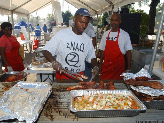 Marcus Woodfork of 2.N.A.Q bar-b-cue of Columbus readies some ribs during the Solid Gold Rib Fest in Zanesville last year.