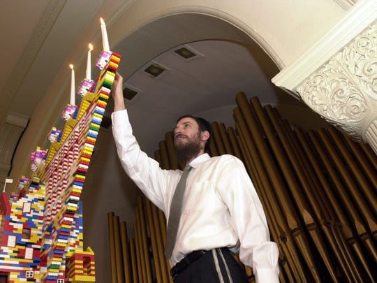 Rabbi Benjy Silverman lights a Menorah which was built out of Legos blocks by the children at the Chabad of the Rivertowns in Dobbs Ferry Dec. 21, 2003.