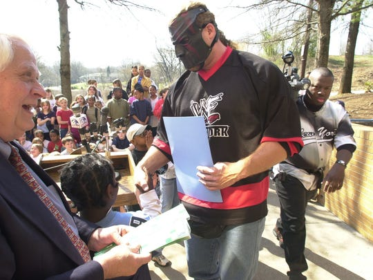 WWF wrestler Kane, aka Glenn Jacobs, shakes hands with kids after giving a fistful of tickets to Vice Mayor Jack Sharp (left). Jacobs was at the South Community Center where the city proclaimed April 16 WWF Day in Knoxville.  The tickets are for kids from the center to attend the WWF event in 2003.