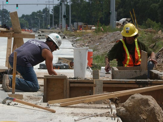 Workers, Christian Moses, left, and David Doucet, right,