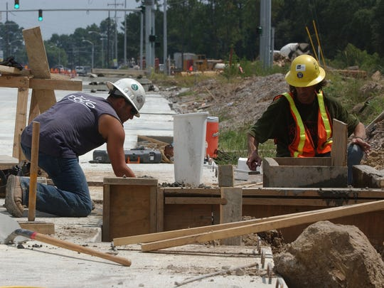 Workers, Christian Moses, left, and David Doucet, right, with Phylway Construction,work on one of the drains, Monday Aug. 9, 2004, in the turning lane for Kaliste Saloom Road to the next phase of Camellia Blvd, which will connect it to Verrot School Road. Photo by Brad Kemp