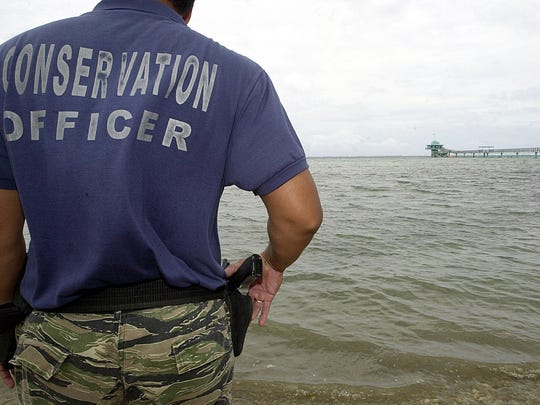 In this file photo, a conservation officer observes the reef area along the Piti Bomb Holes Marine Preserve.