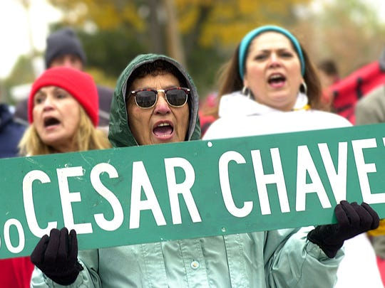 Margarita Noyola holds a Cesar Chavez Avenue sign as she and others march down Kalamazoo Street to a rally to support the naming of the street to Cesar Chavez Avenue in 2002.