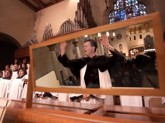 Lee Gwozdz conducts Grace Cathedral's choir during a Sunday service.