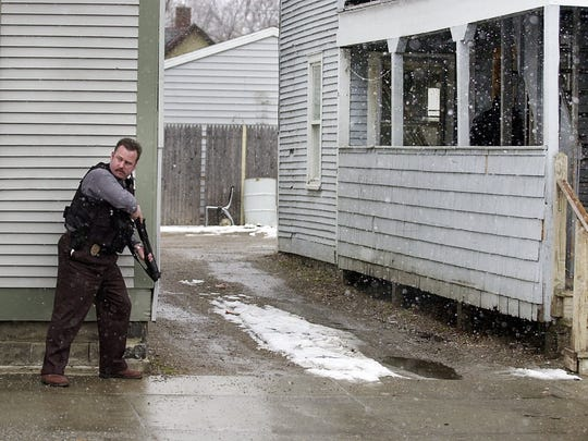 Former Burlington Police Department Cpl. Dave Scibek (left) seen in March 2002, covering fellow officers as they enter a residence at 57 North Street in Burlington.