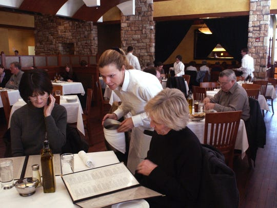 This 2004 file photo of Biaggi's shows server Kristy Hevert (center) with first-time customers Mary AnnEvans (left) and Maryann Firlit (right).
