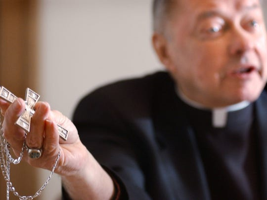 Bishop John Kinney shows the pectoral cross he received during his trip to the Vatican to meet with Pope John Paul II in 2004.