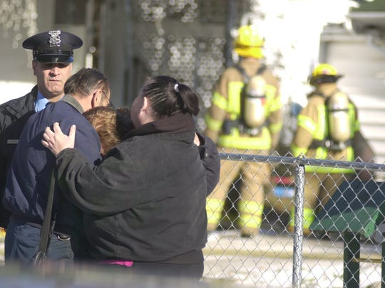 Mary Fuller cries on the shoulder of Kenneth Fuller with Michelle Fuller after learning two of her grandsons perished in a house fire in January 2002.