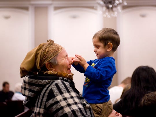 "Maria Ponomarenco has her nose squeezed by grandson Vitale Malac, 2, before the start of the Grace of Christ Slavic Baptist Church's ""Back to Bethlehem"" program last Saturday night."