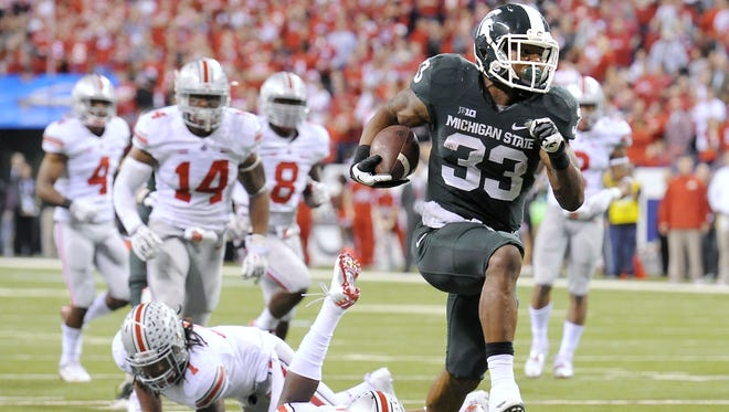 MSU's Jeremy Langford breaks through the Ohio State defense for MSU's final touchdown in their  34-24 win in the 2013 Big Ten Championship.
