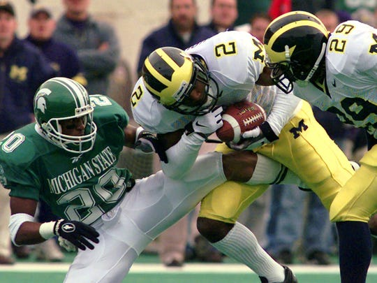 Michigan cornerback Charles Woodson intercepts a pass intended for Michigan State receiver Octavis Long as Marcus Ray looks on during the fourth quarter at Spartan Stadium in East Lansing on Oct. 25, 1997.