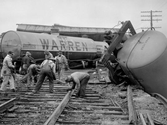 Men work to clear the tracks over Treadaway Boulevard Jan. 10, 1958, after 28 cars derailed.