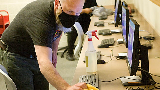 Byrun Reed disinfects a computer keyboard on the first day patrons were allowed to enter Rodman Public Library during the COVID-19 pandemic. The library has instituted various safety measures such as barriers, cleaning processes and requiring all visitors and employees to wear face masks.