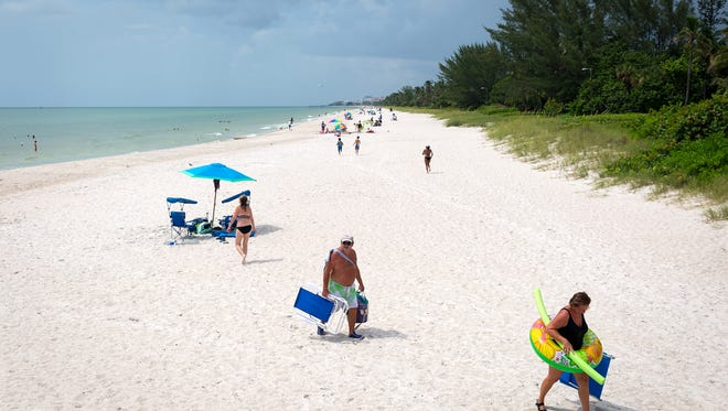 Beachgoers circulate near the Naples pier on Wednesday, July 27, 2016, in Naples. The Dutch travel website TravelBird ranked Naples as 38th most expensive out of 250 beaches worldwide by calculating the average cost for sunscreen, a bottle of water, a beer, ice cream, lunch and any applicable access fees.
