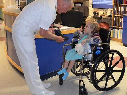 Wilmington, N.Y., resident Kareena Winch, right, a patient at the University of Vermont Children's Hospital, gives the thumbs up to Navy Vice Adm. Tom Rowden before she received her USS Decatur hat.